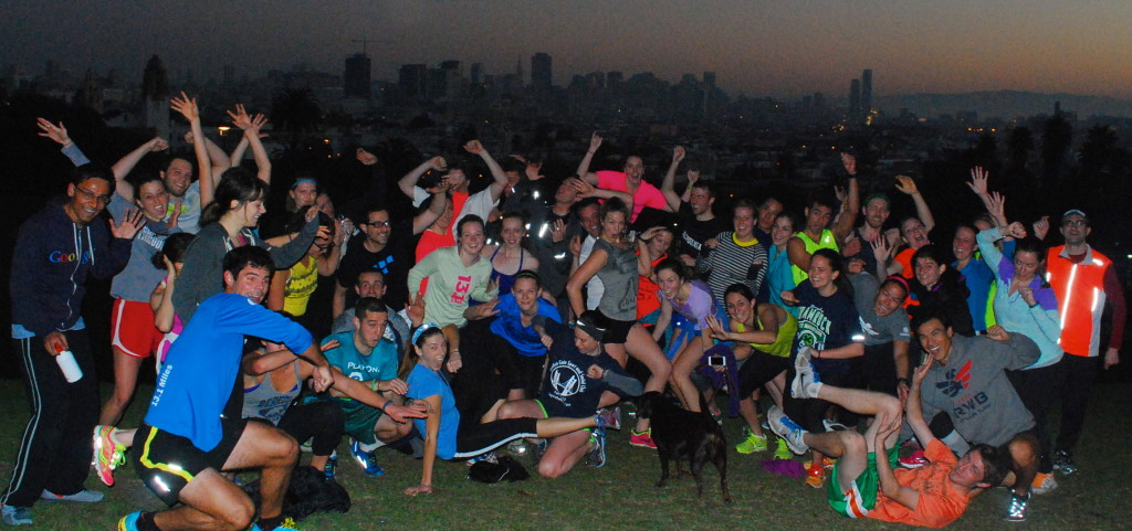 November Project San Francisco group photo at Dolores Park just before sunrise, the barely backlit outline of the downtown skyline visible behind them.