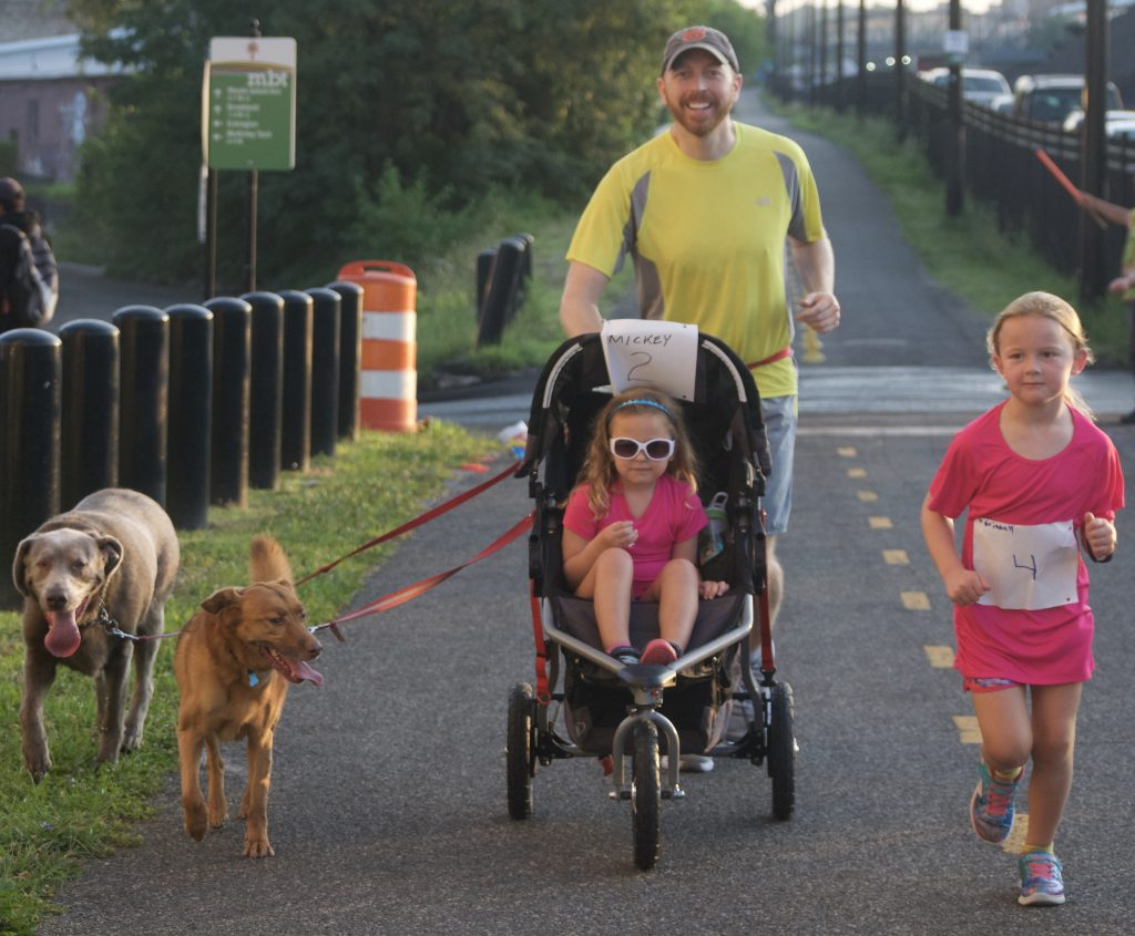 A man runs with a daughter in a stroller, another daughter to his left, and two dogs on leashes to his right.