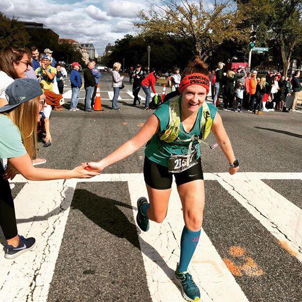 Carrie high fives a person as she runs past the cheer station. She is smiling.