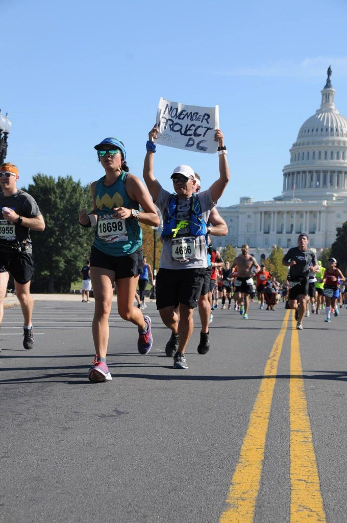 """Kuang runs with a sign that reads """"November Project DC."""" Behind him is the Capitol building."""