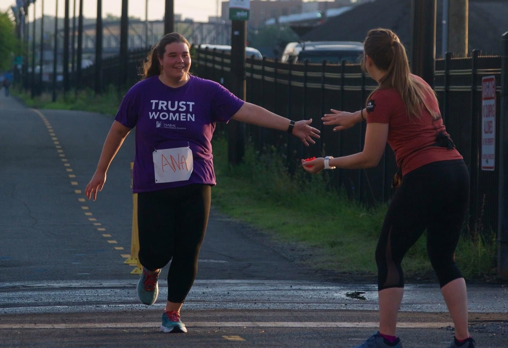 Ana Little Sana running a sunrise 6K in a purple teeshirt and giving someone a high-five