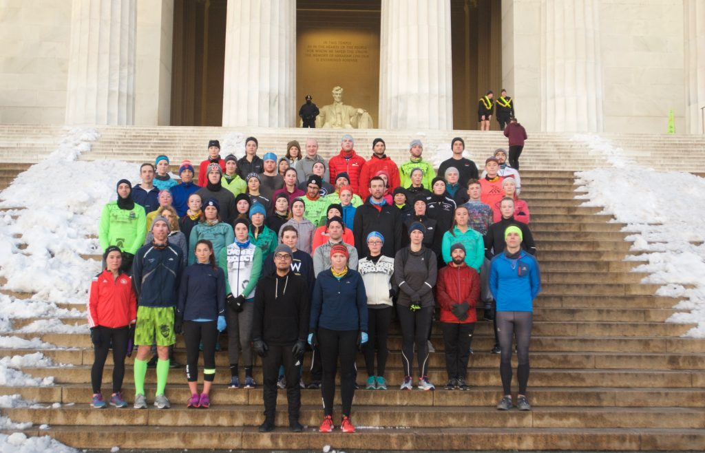 Group photo on the stairs of Lincoln Memorial with snow on both sides of the group of standing humans.