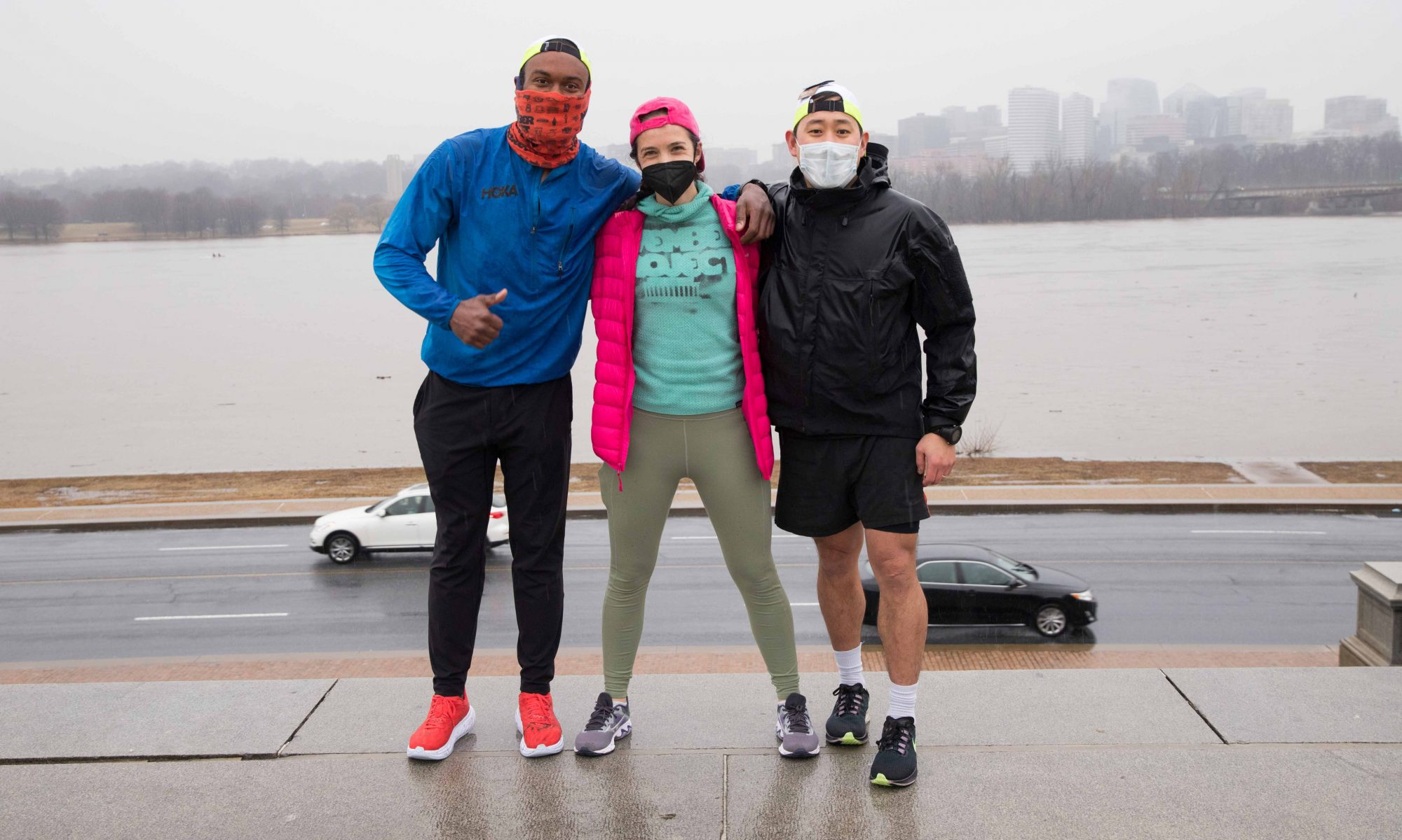 An image of Chris Jolly, Katherine Foley, and Young Joo standing in front of the stairs behind the Lincoln on a grey day. Everyone is wearing masks.