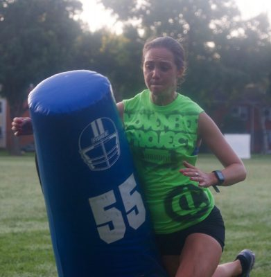 Katherine Foley in a lime green tank top running into a football tackling dummy.