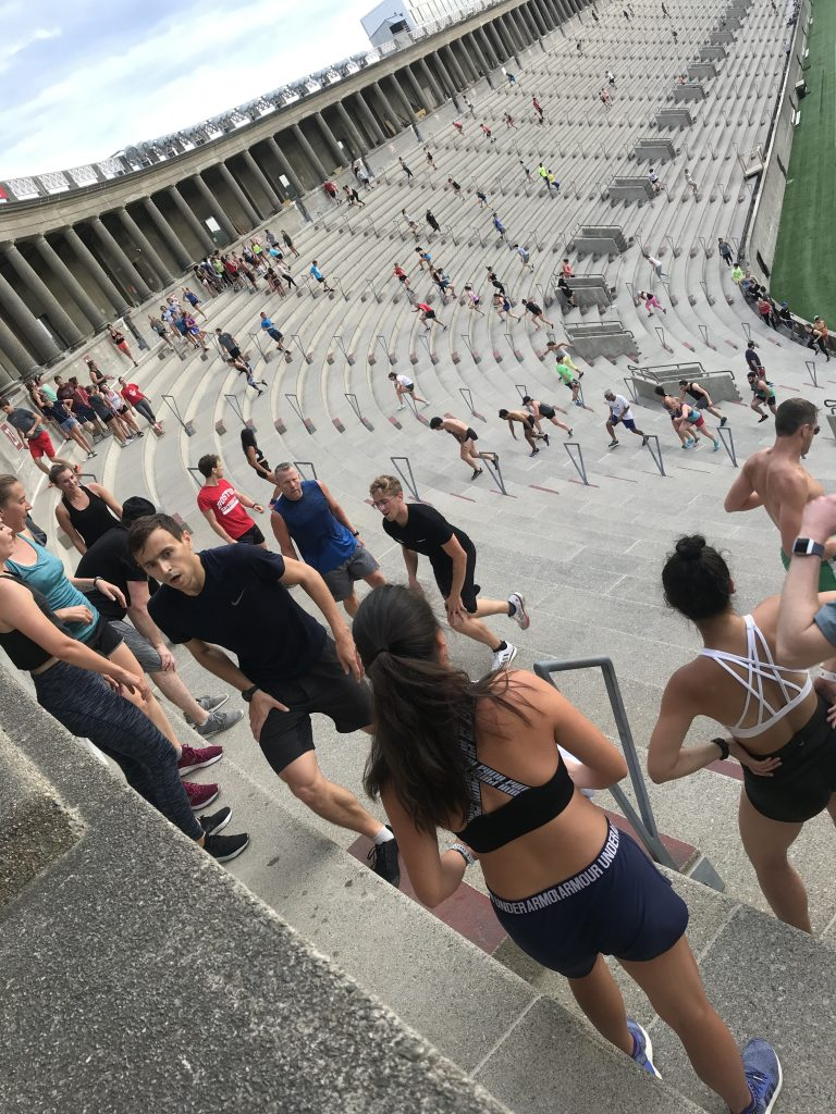 Many people climbing stairs in Harvard stadium, a colosseum-like structure. Everyone is working hard.