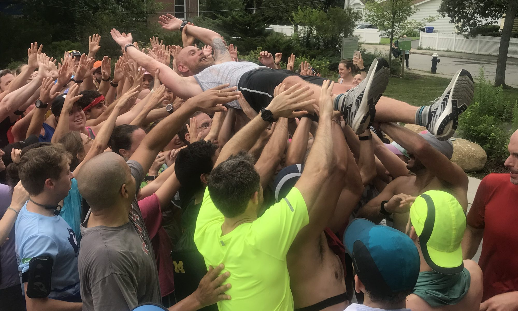 A crowd of people with arms raised up to crowd surf one man. The man is one of the co-founders of November Project and he has his arms raised up above his head and is smiling, wearing Brooks shoes.