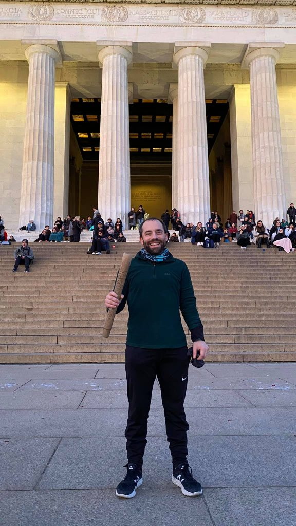 Mike stands with the Positivity Award in front of the Lincoln Memorial.