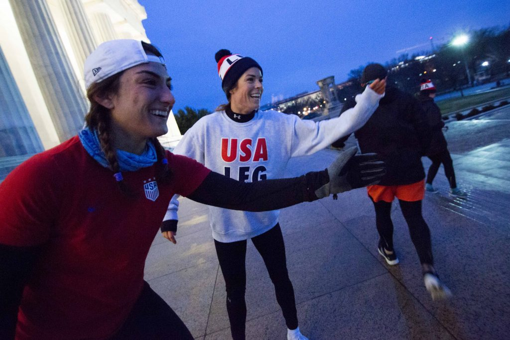 Kelley O'Hara hands out high-fives at the top of the Lincoln Memorial