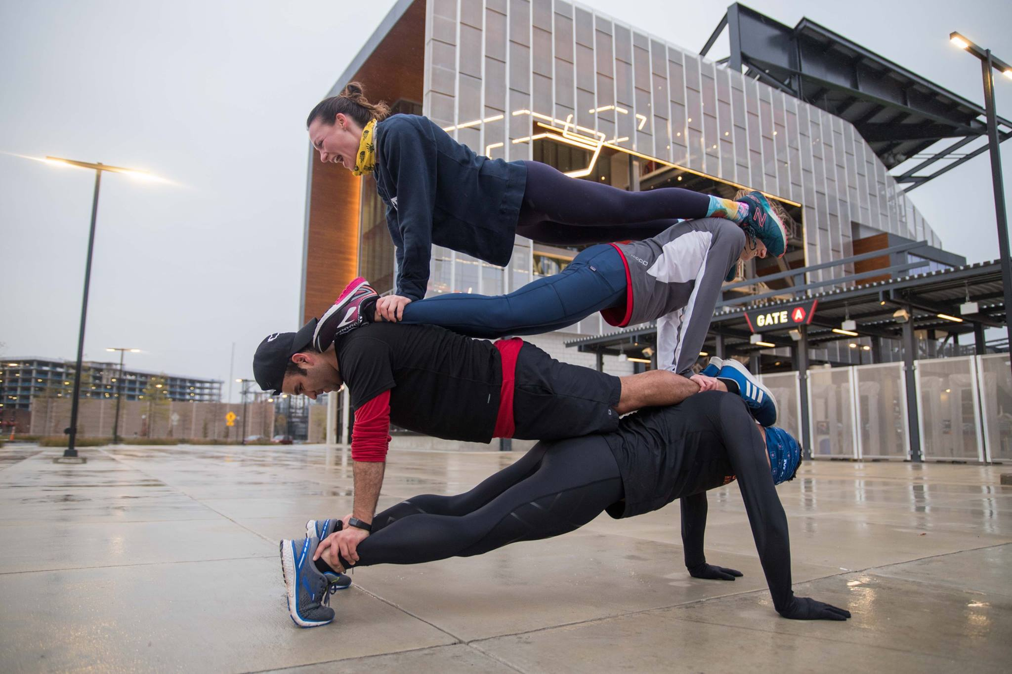 Four November Project DC tribe members partner on wet concrete outside Audi Field. Each person is stacked on top of the person below them like a plank sandwich. Ron Batcher is on the bottom of the plank pile. The tribe members are smiling and laughing.
