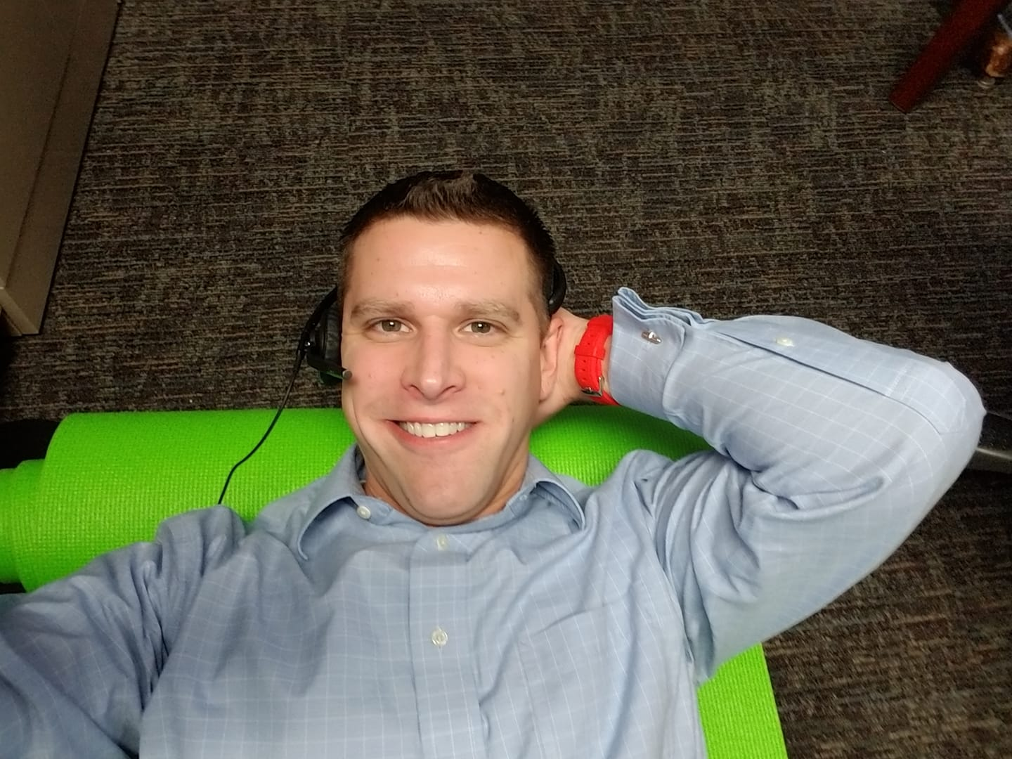 Ron Batcher leans back on a lime green yoga mat and smiles at the camera. He is wearing a headset at work while doing crunches for Abvember.