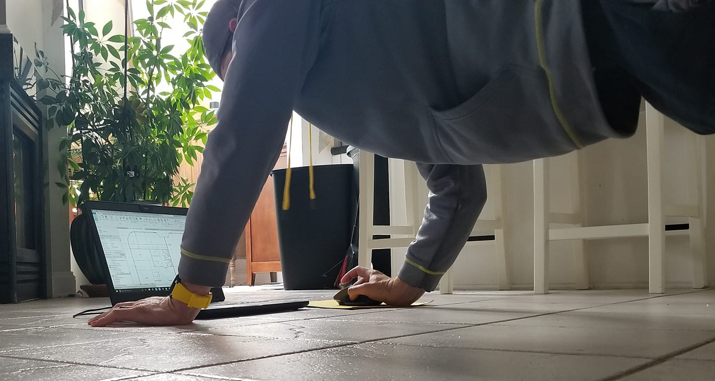 Ron Batcher is pictured in plank position while working on his laptop in his home.