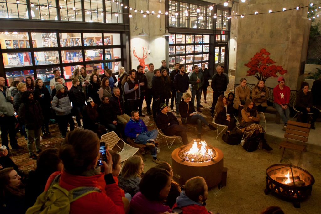 Hundreds of people are gathered around two fire pits as they listen to a person tell a story.