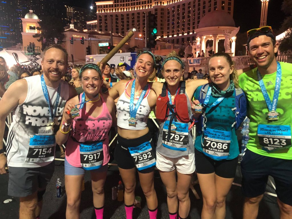 Six people hold their medals and smile after a half marathon.