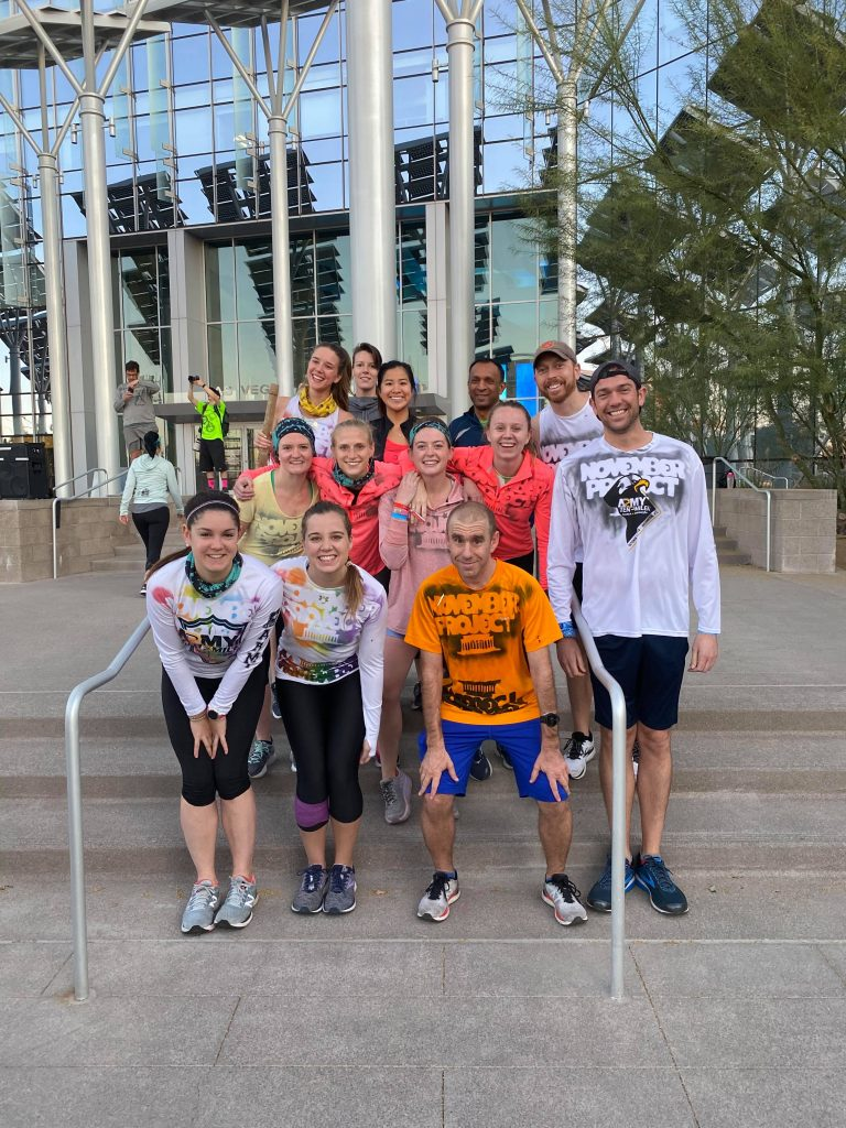 13 people, mostly from DC, smile after doing a workout at City Hall.