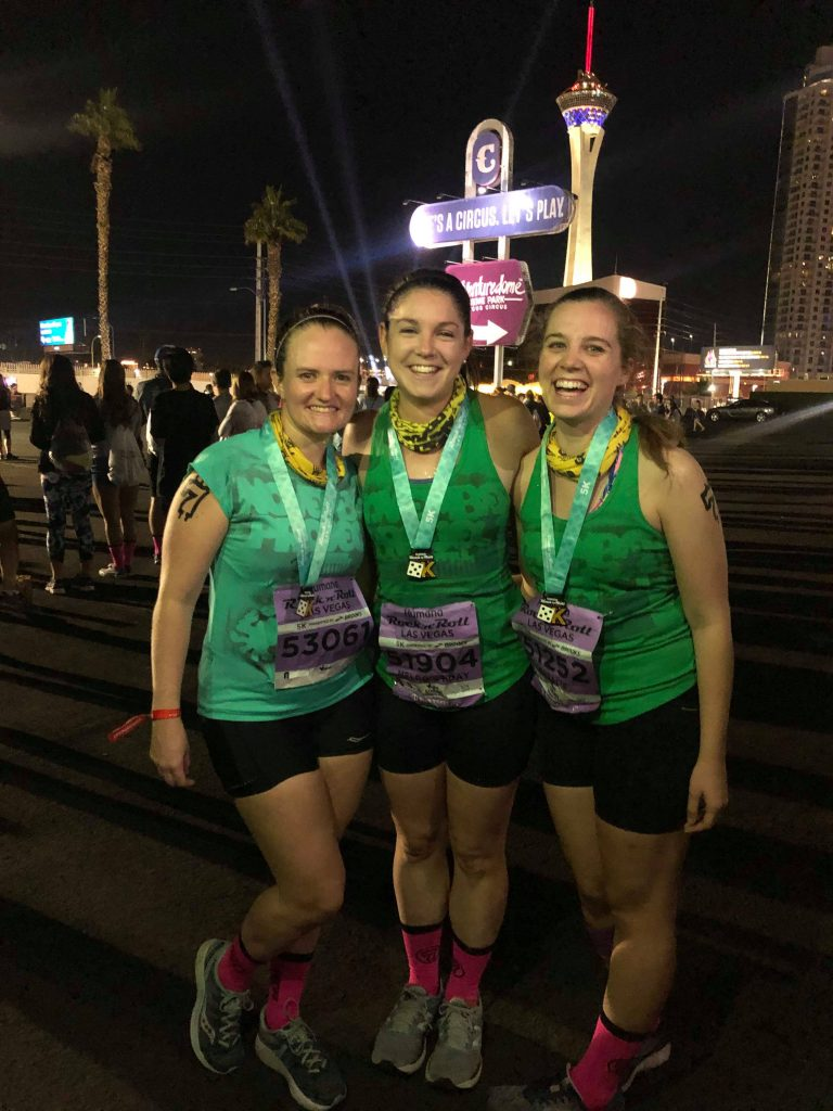 Three women in matching green shirts and pink socks.