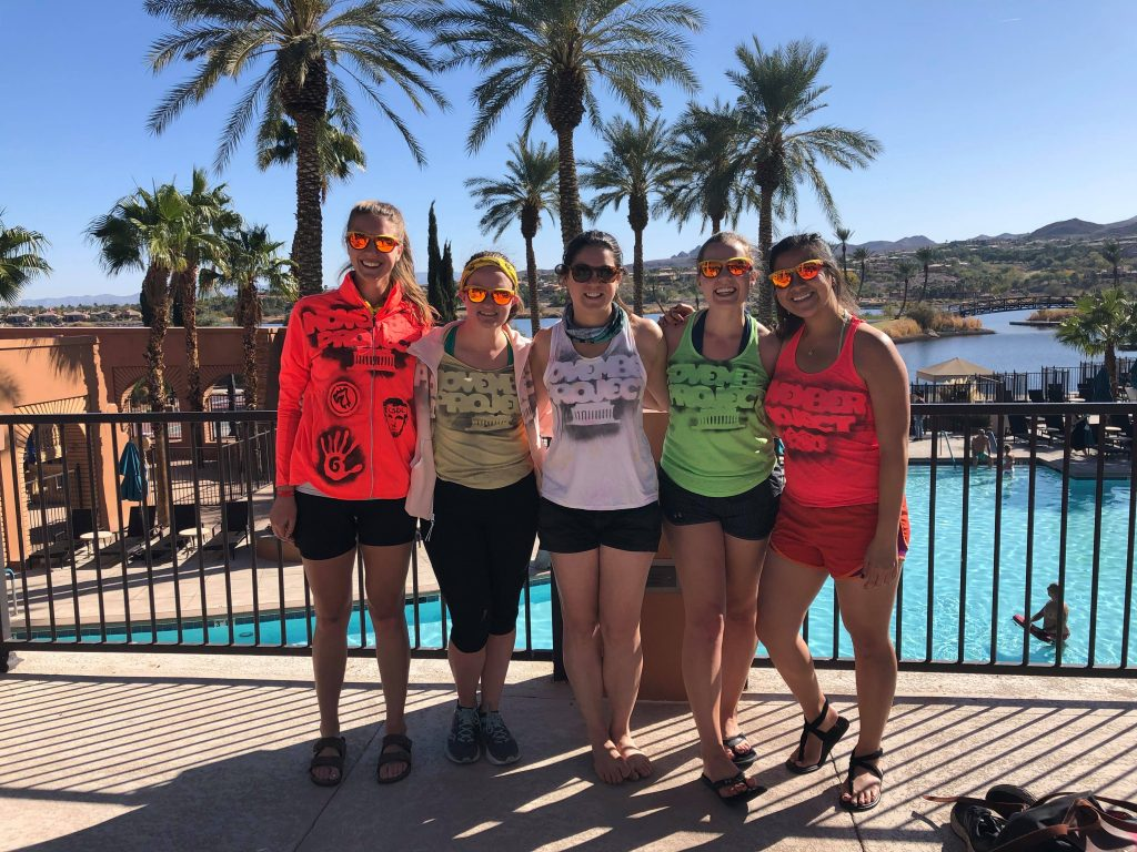 Five women in grassroots gear hang out above a swimming pool.