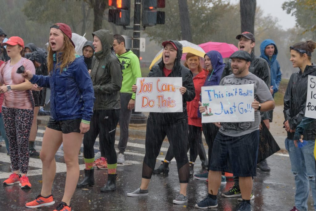 People hold signs and cheer loudly while getting drenched by rain.
