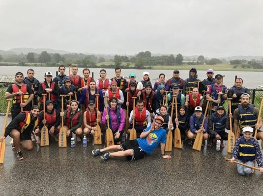 Group photo of roughly 30 people from NPDC in front of the Anacostia River. Everyone is wearing rain coats and holding boat oars in their hands.