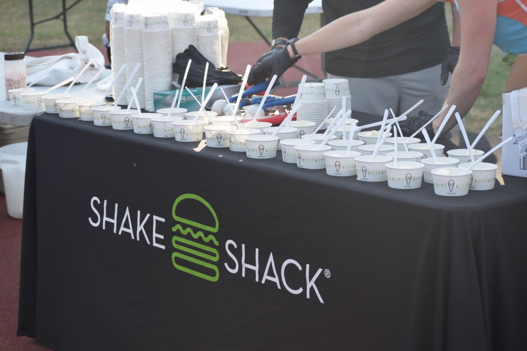 Scoops of Shake Shack custard sit in cups on a table waiting for runners to grab them.