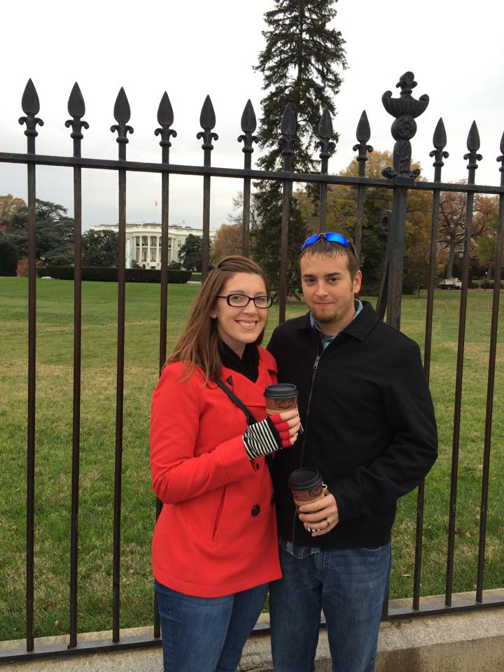Jason and Anne are posing in front of the White House