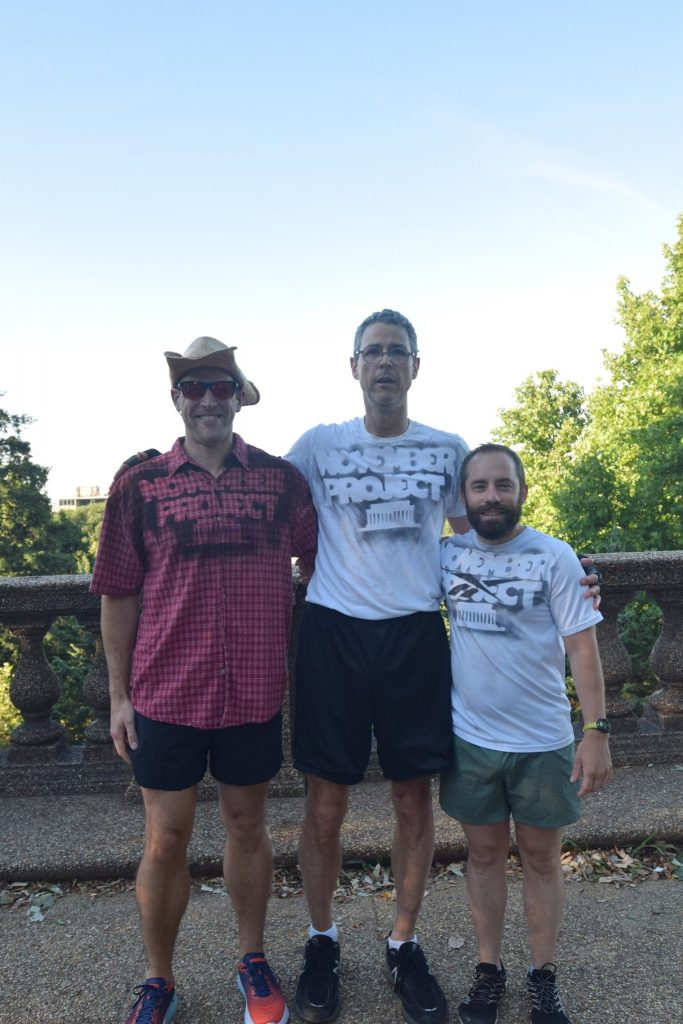 Mike stands and smiles with his friends Ron and Ken after they guest led a workout.