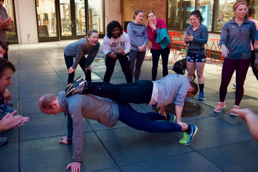 Mike does a partner plank with his friend Thomas while others look on all around them.
