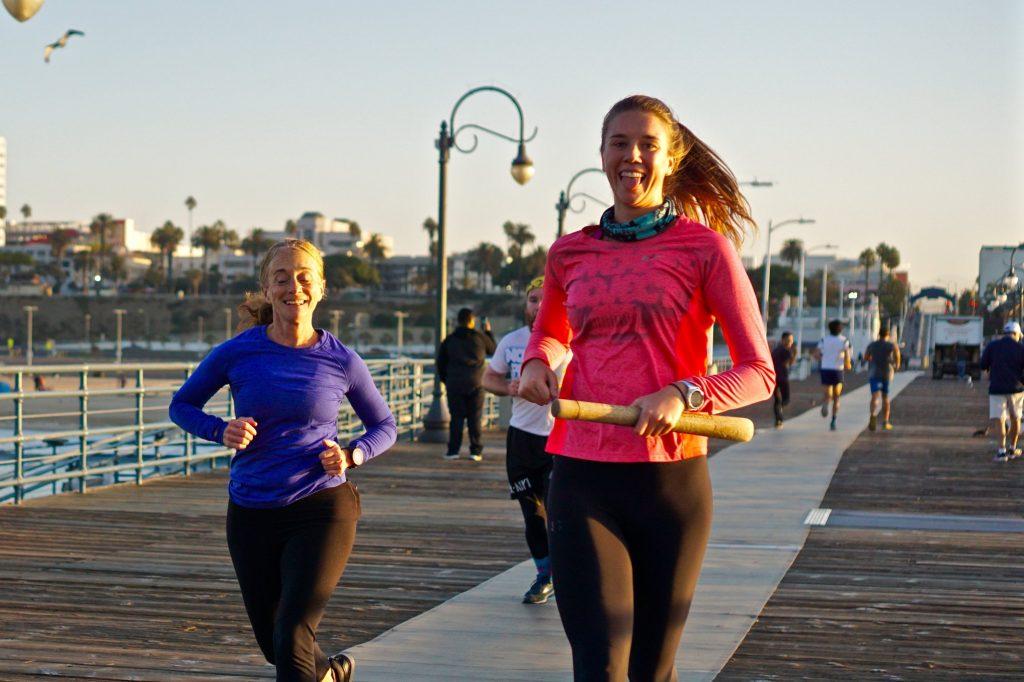 Hannah runs with the Positivity Award on a pier in LA.