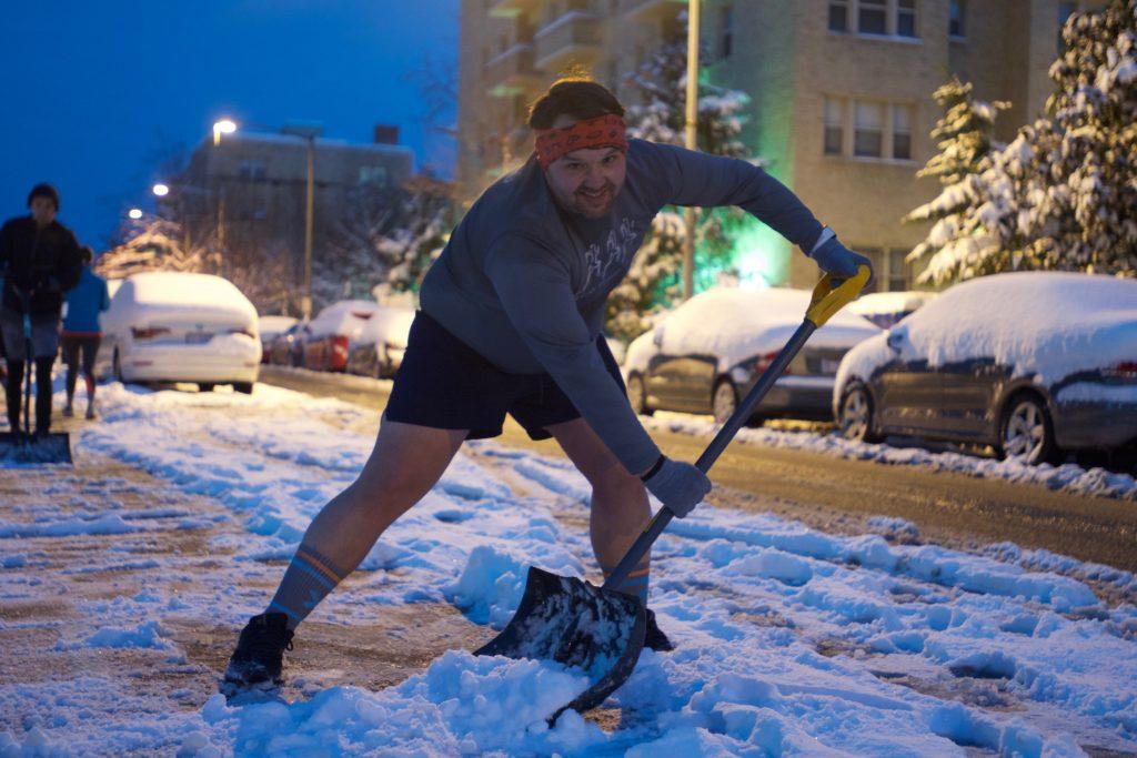 A man shovels snow while wearing shorts!