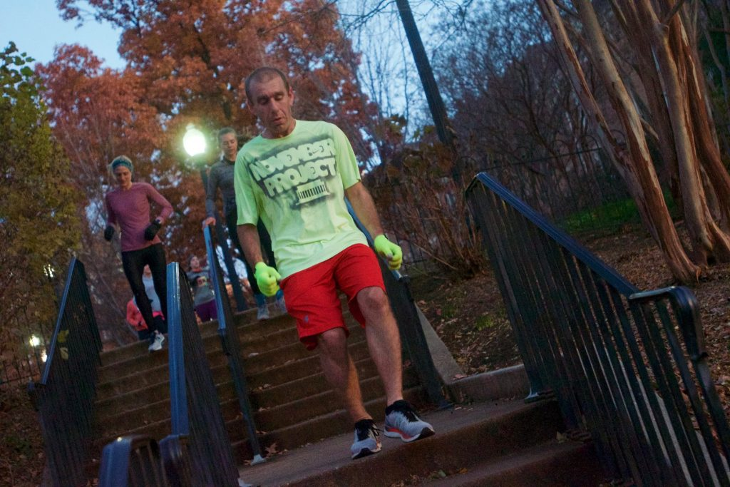 Alex runs down a set of stairs with iron railings on either side of him. He wears red shorts, and a neon green shirt and gloves.